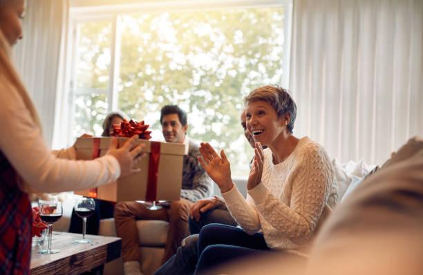 kleines mädchen überraschend ihre großmutter mit einem weihnachtsgeschenk - geschenke eltern weihnachten stock-fotos und bilder