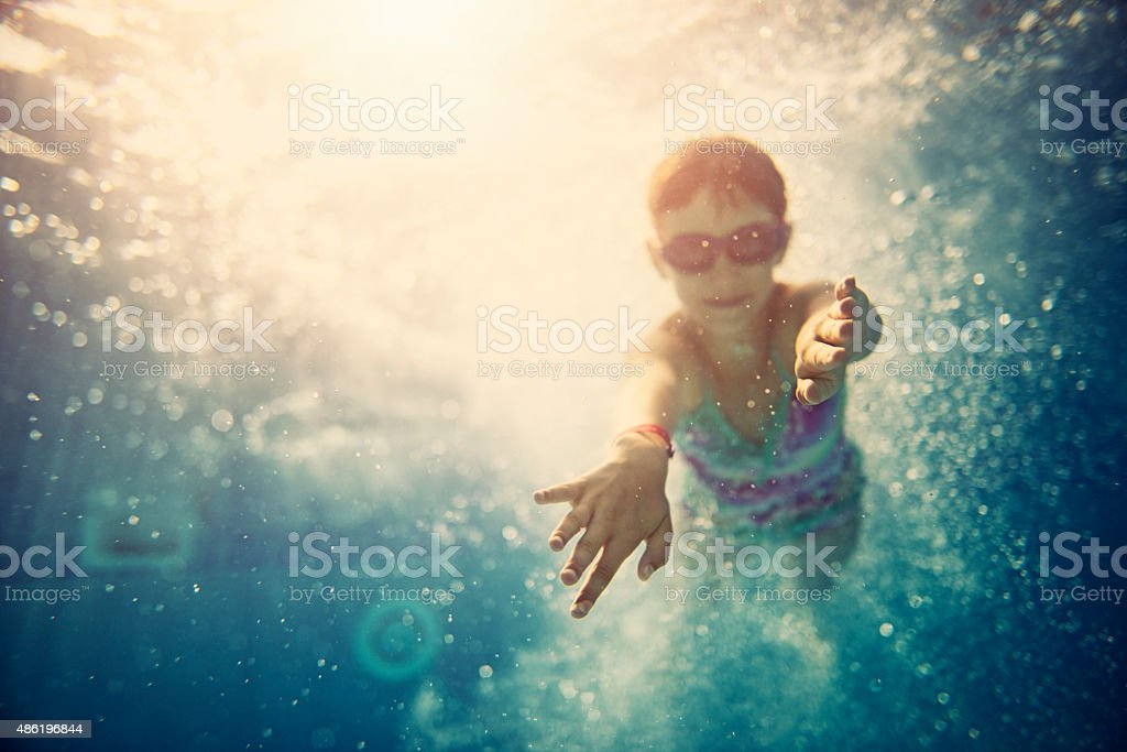 Little girl swimming underwater stock photo