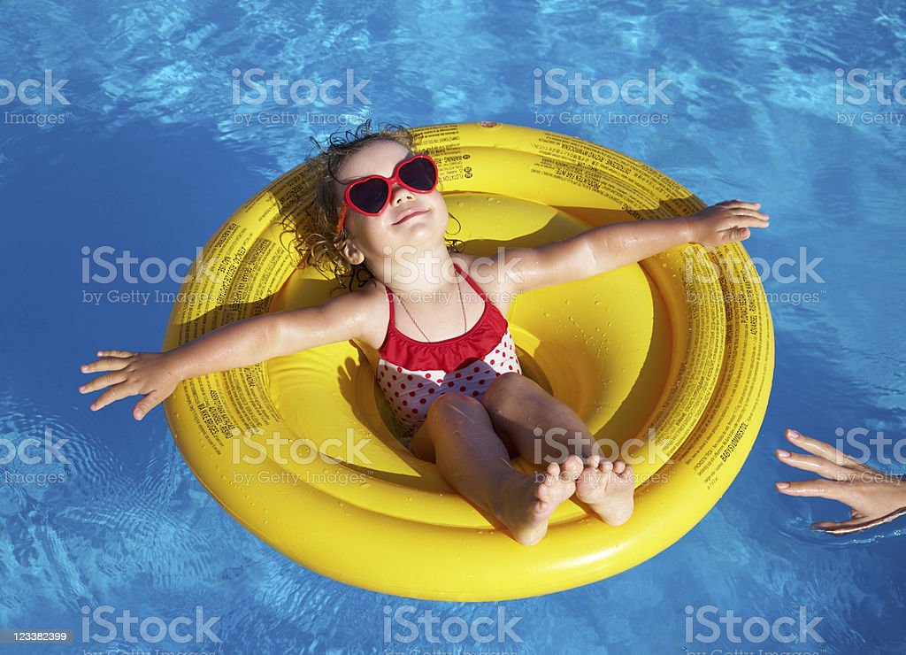 Little girl swims in  pool stock photo