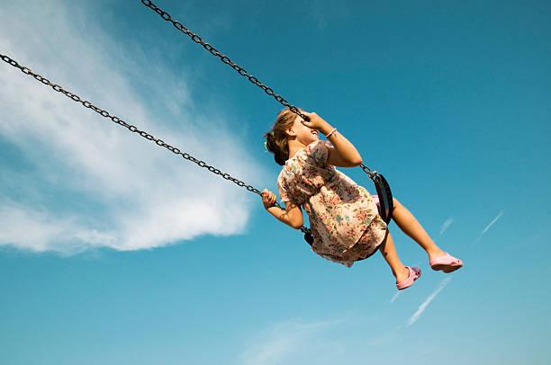Little Girl Swinging Against Blue Sky stock photo