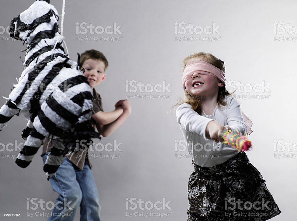 Kleines Mädchen schwingen im Piñata Lizenzfreies stock-foto