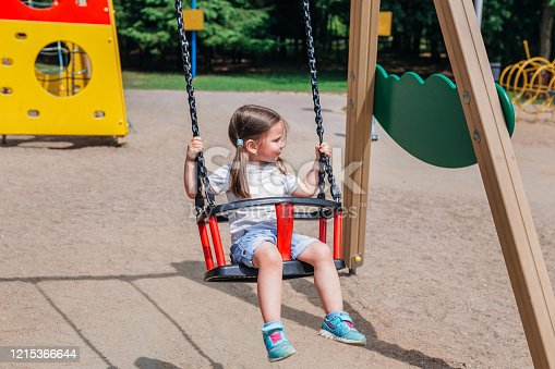 Little cute girl swinging at playground outdoors in summer