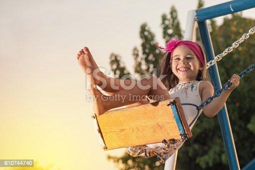 istock Little Girl Swinging At Sun Set 610744740