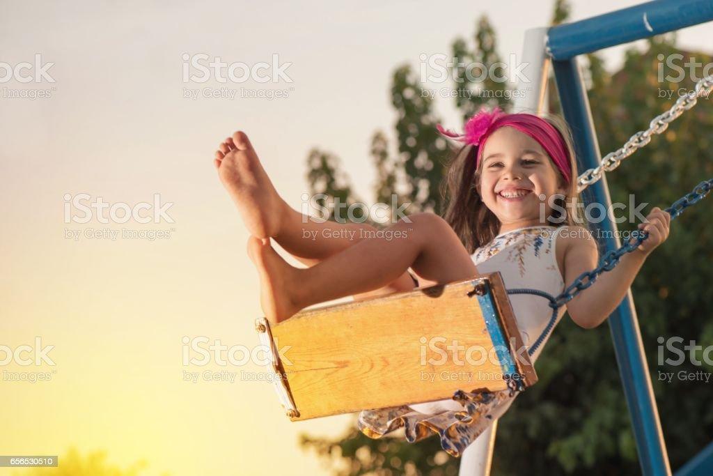Little Girl Swinging At Sun Set - foto stock