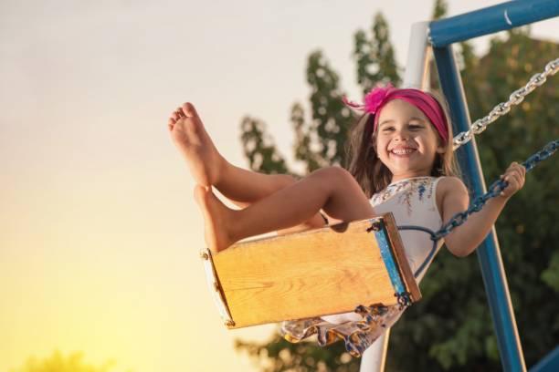 little girl swinging at sun set - balouço imagens e fotografias de stock