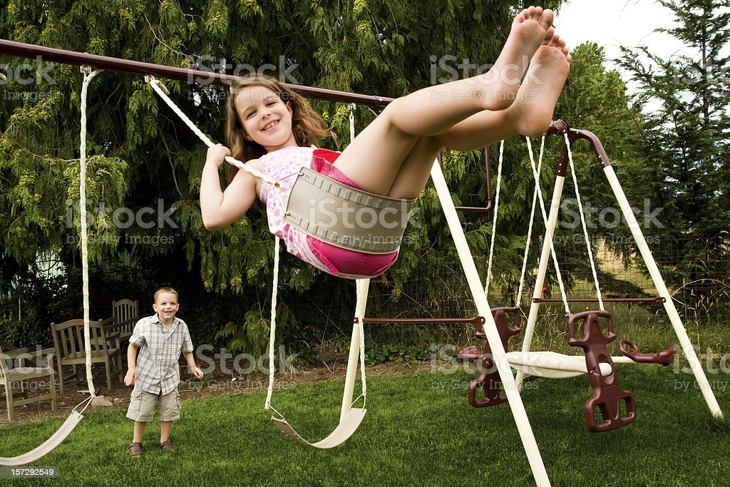 Little Girl Swinging In Her Backyard With Younger Brother ...