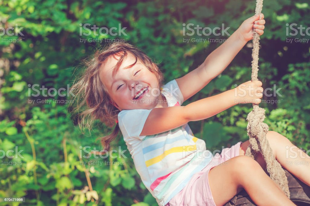 Little girl swinging in summer stock photo