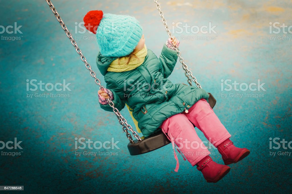 little girl swinging on a swing stock photo