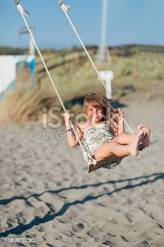 One child swinging on a swing set, playing on the beach on a beautiful sunny day