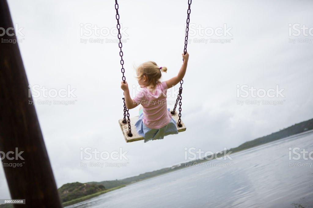 Little girl swinging on a wooden swing stock photo