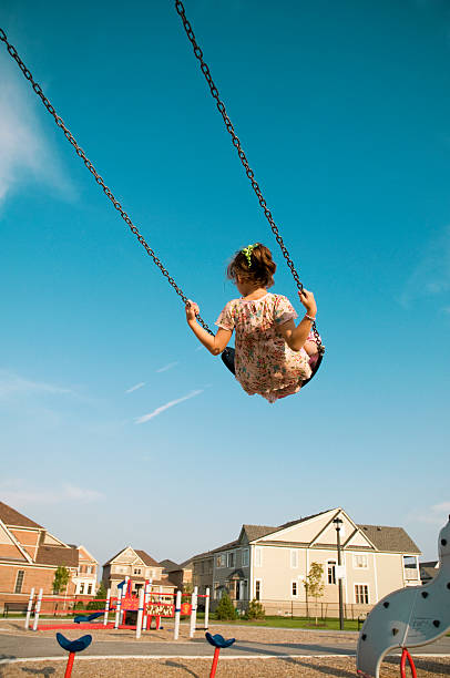 Little Girl Swings, Playground in the Suburbs stock photo