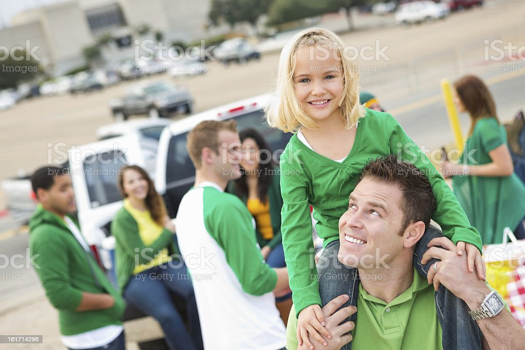 Little girl tailgating with dad at college football stadium stock photo
