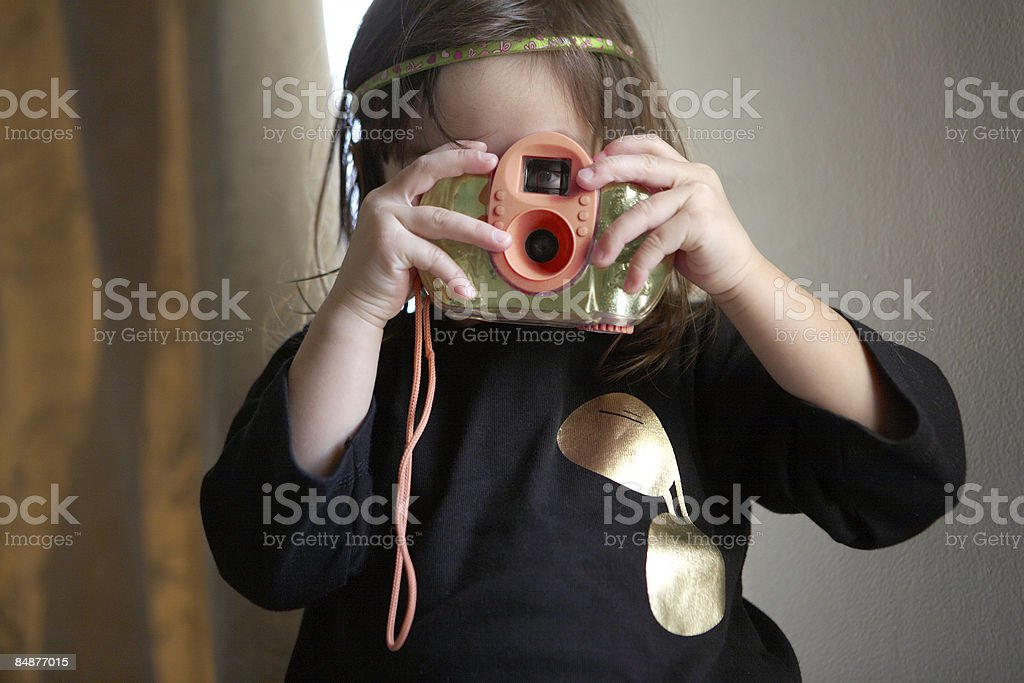 little girl taking a picture with a toy camera royalty-free stock photo