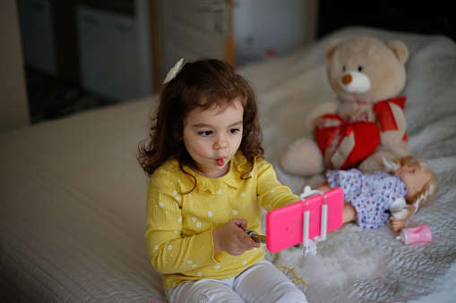 Little girl taking a selfie with her new toy mobile camera stock photo