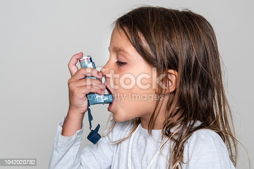 Caucasian Little girl taking her asthma medicine