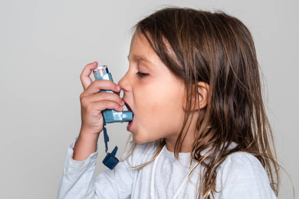 Little girl taking her asthma medicine stock photo