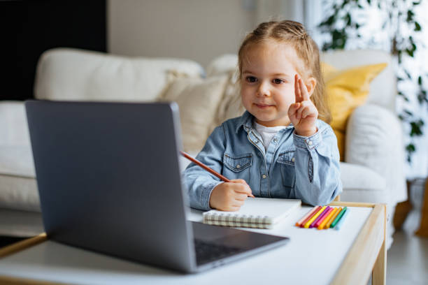 Little girl taking online courses in living room Little girl taking online courses in living room desolation stock pictures, royalty-free photos & images