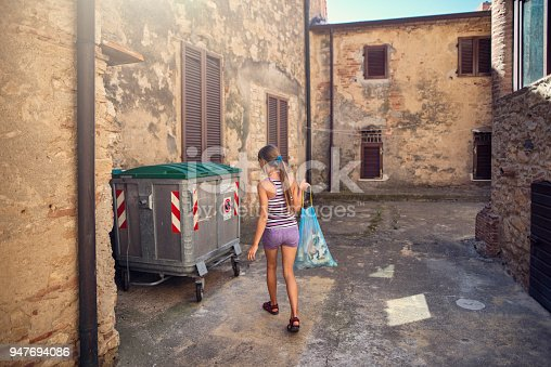Little girl taking out garbage in small italian town.  Nikon D800