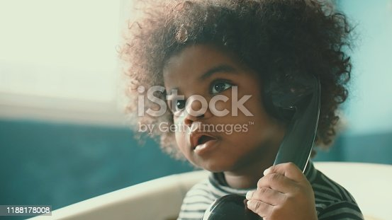 African-american girl(2-3 years) sitting on vintage chair and using rotary phone, Bangkok Thailand