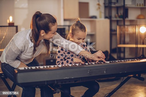 Little girl teaching to play synthesizer in music school