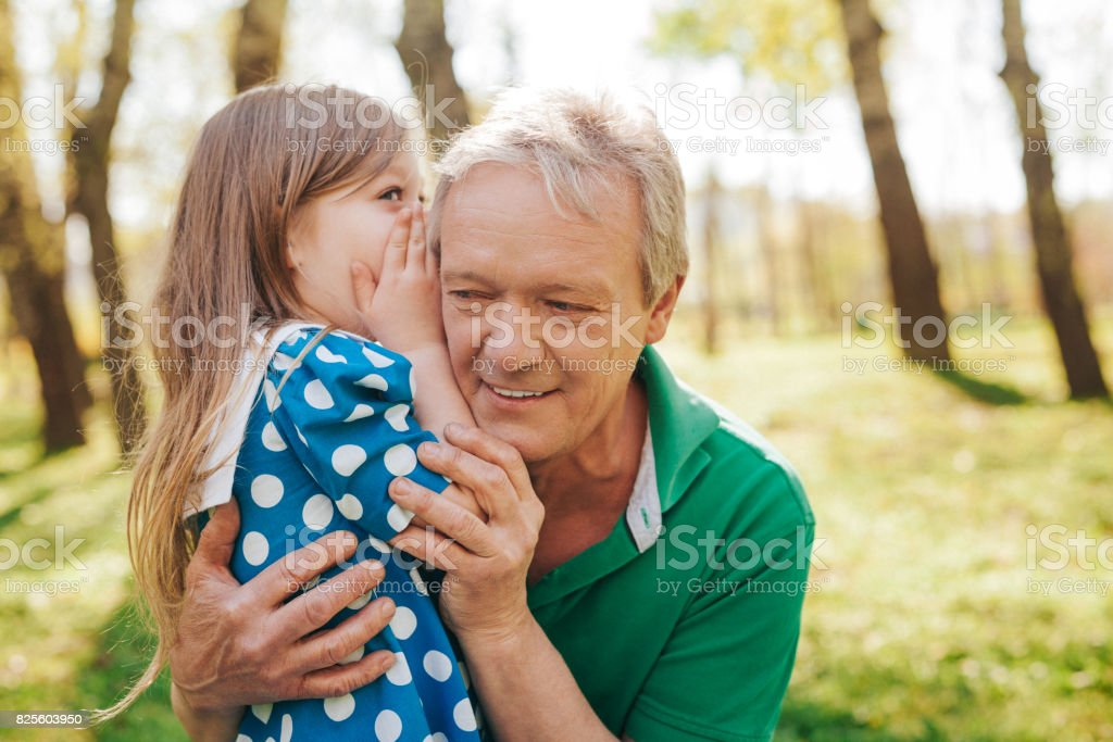 Little girl telling secret to grandpa stock photo