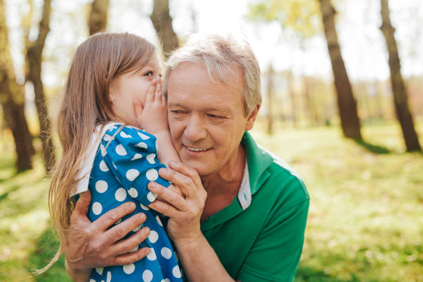 little girl telling secret to grandpa - listening stock photos and pictures