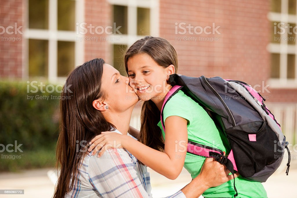 Little girl tells mom goodbye on first day of school. stock photo