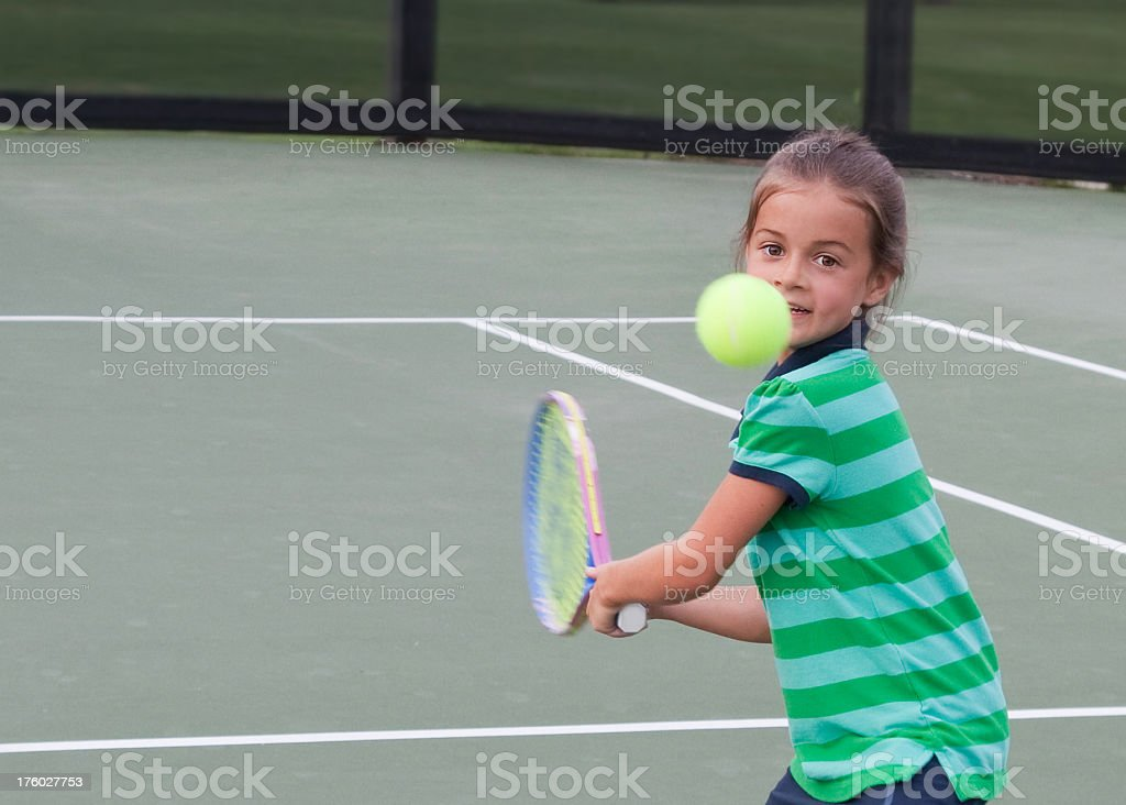 Little Girl Tennis Player Focused on Hitting the Ball royalty-free stock photo