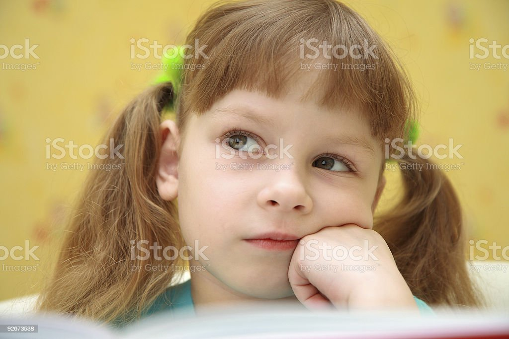 Little girl thinking by opening book royalty-free stock photo
