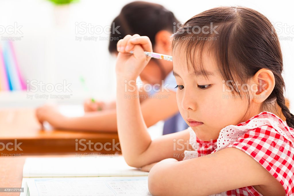 little girl thinking in the classroom royalty-free stock photo