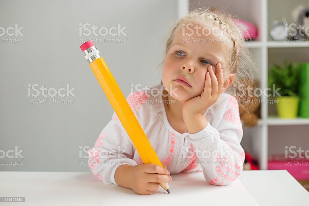 Little girl thinking while writing with big pencil stock photo
