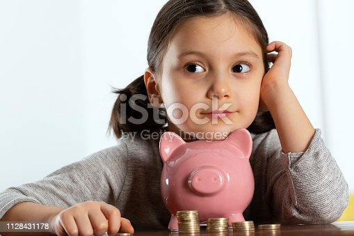 Little girl thinking her investment with piggybank at the table.
