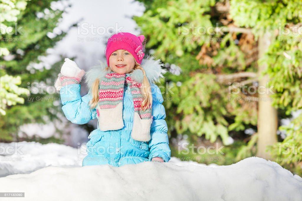 Little girl throw snowball hiding behind snow wall stock photo