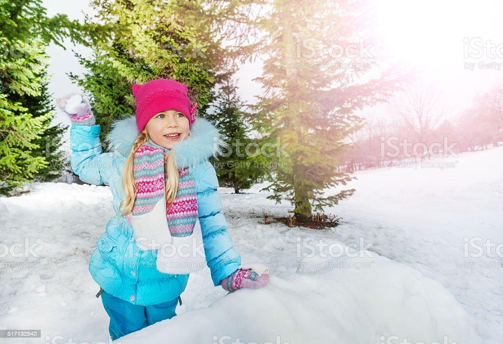 Little girl throw snowball in park stock photo