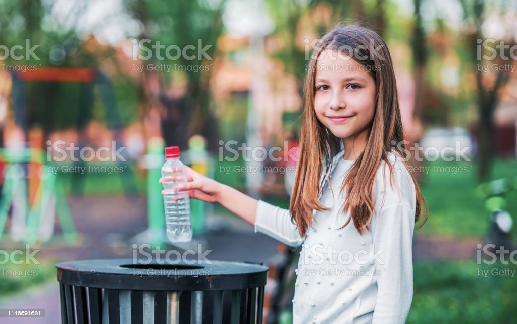 Little girl throwing bottle into the trash. Ecology concept Take care about your environment. Little girl throwing bottle into the trash. Ecology concept Active Lifestyle Stock Photo