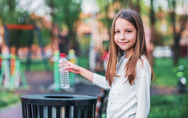 Kleines Mädchen wirft Flasche in den Papierkorb. Ökologie-Konzept – Foto