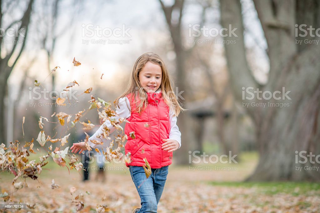 Little Girl Throwing Leaves stock photo