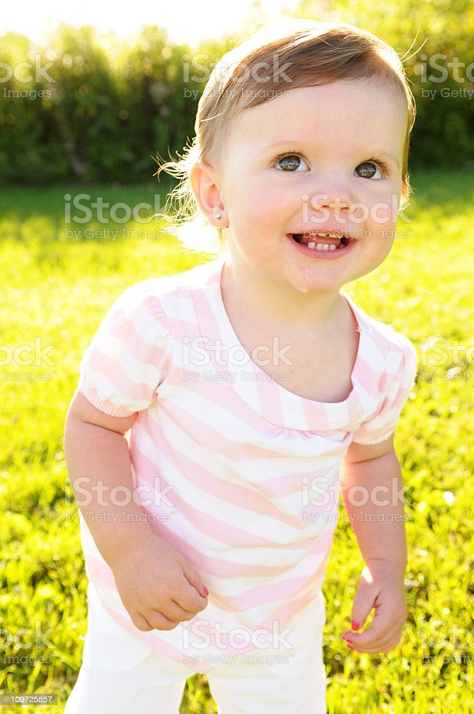 Little Girl Toddler Smiling and Standing in Grass royalty-free stock photo