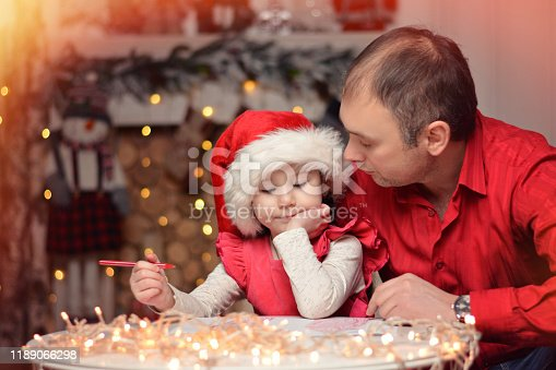 1062609644istockphoto Little girl together with dad write a letter of wish to Santa Claus. Christmas. New Year. 1189066298