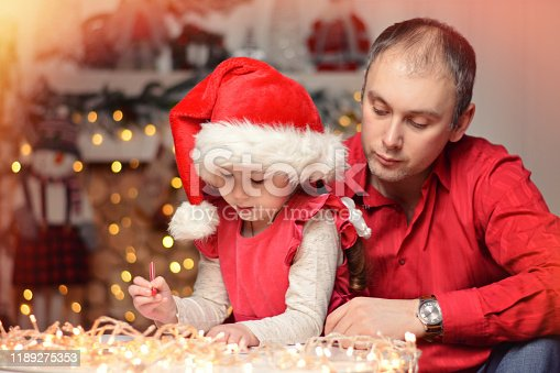 1062609644istockphoto Little girl together with dad write a letter of wish to Santa Claus. Christmas. New Year. 1189275353
