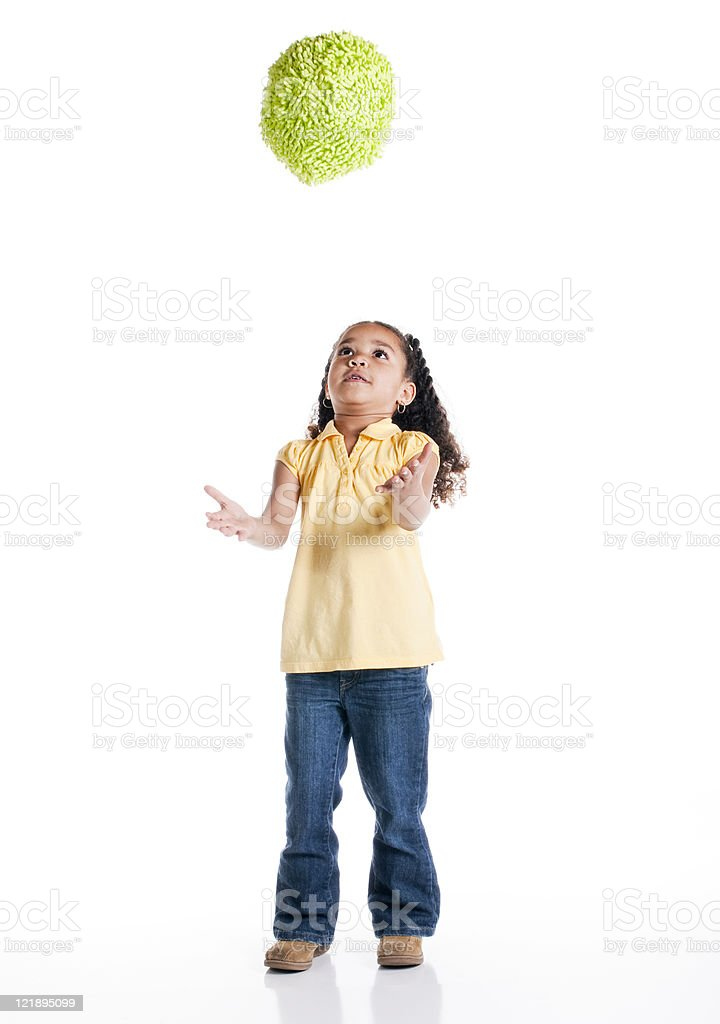 Little Girl Tossing a Ball on White Background royalty-free stock photo