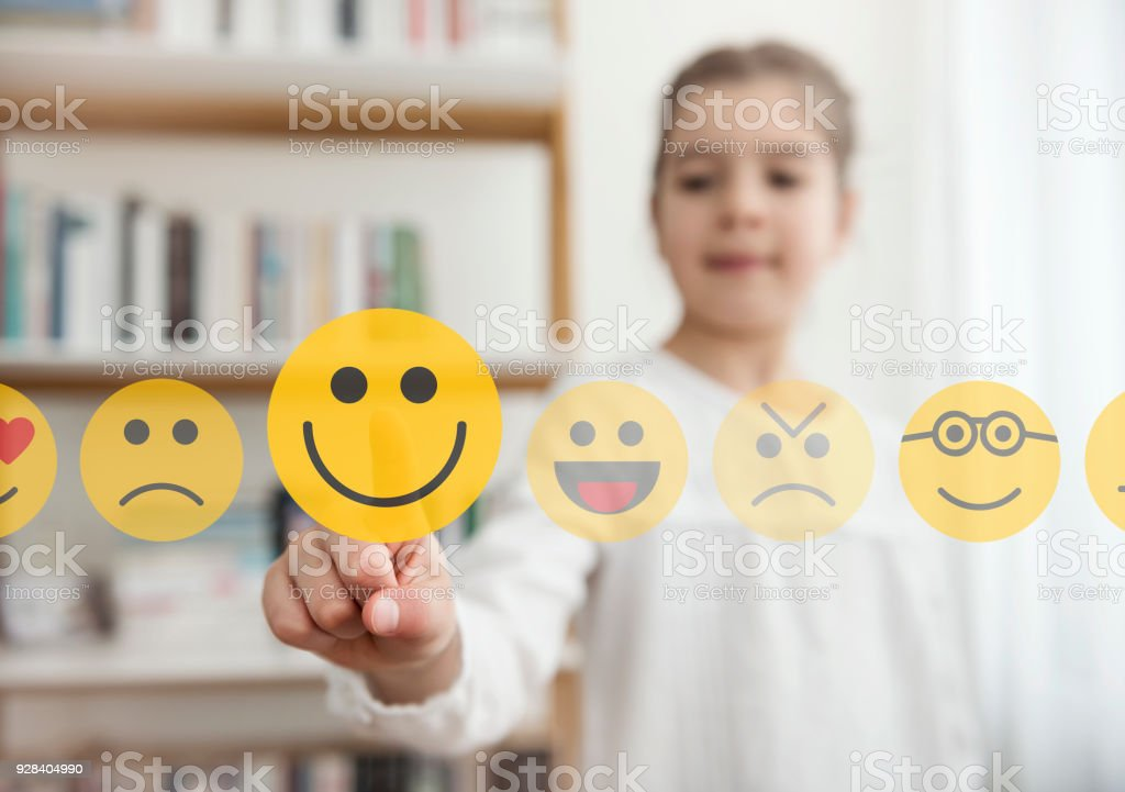 Little girl touching the smiley emoji icon on the touch screen – zdjęcie