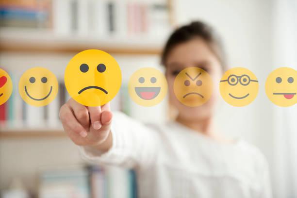 Kleines Mädchen, das die unglückliche Gesicht-Emoji-Ikone auf dem Touchscreen berührt – Foto
