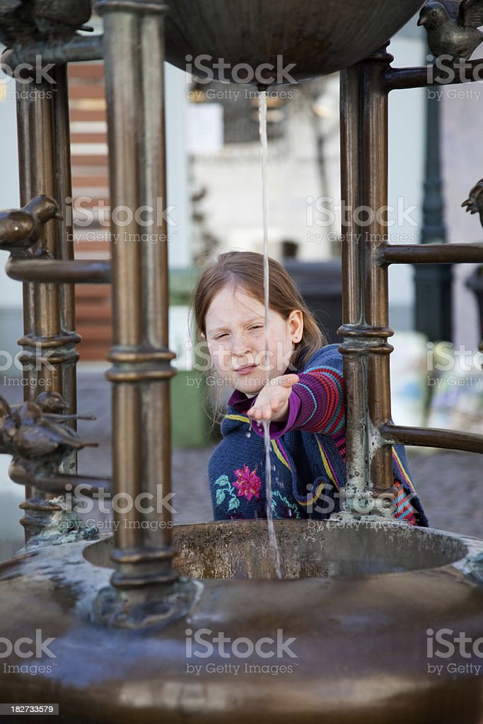 "Little girl touching water at the fountain ""7 year old girl, playing with water at a fountain."" 6-7 Years Stock Photo"