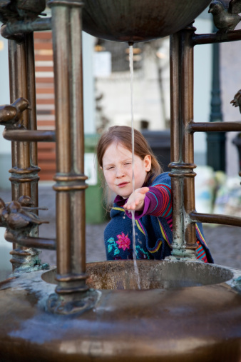 Little Girl Touching Water At The Fountain Stock Photo - Download Image Now