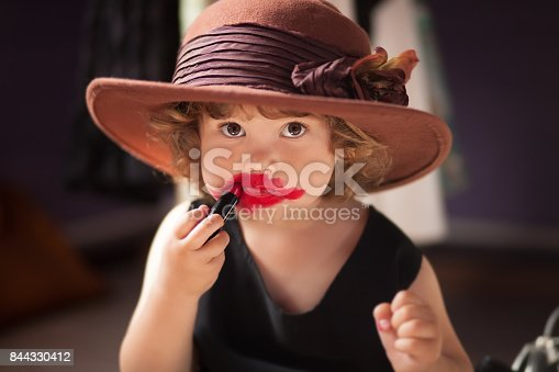 istock Little girl trying mom's lipstick. Growing up concept. 844330412