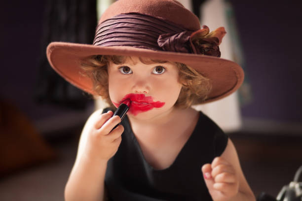 Little girl trying mom's lipstick. Growing up concept. stock photo