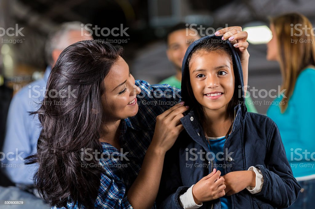 Little girl trying on coat at winter clothing donation drive stock photo