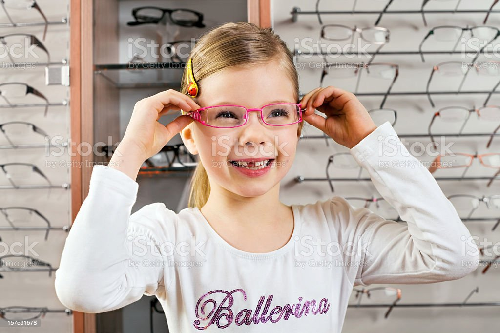 Little Girl Trying On Glasses At Opticians  6-7 Years Stock Photo