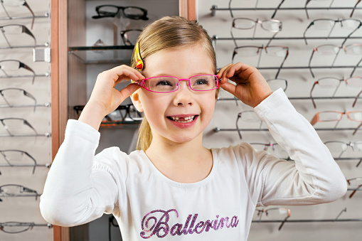 Little Girl Trying On Glasses At Opticians Stock Photo - Download Image Now